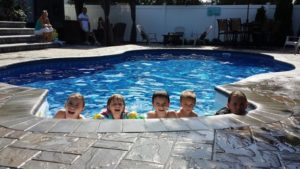 Want to know how to create the coolest backyard every? Try adding a pool to your backyard, like this Radiant inground pool these children are playing in.