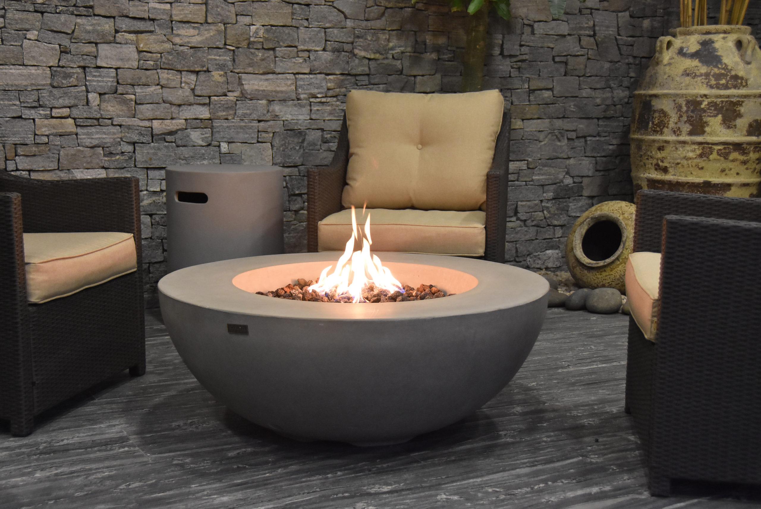 Elementi fire pit in a backyard with patio furniture